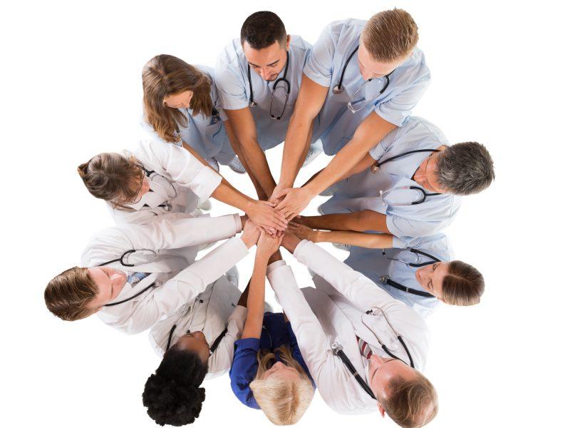 medical team holding hands together